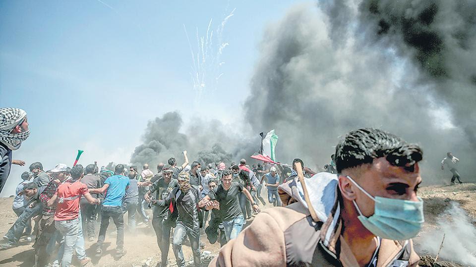 Manifestantes corren para protegerse del gas lacrimógeno anteayer en la frontera entre Israel y la Franja de Gaza.