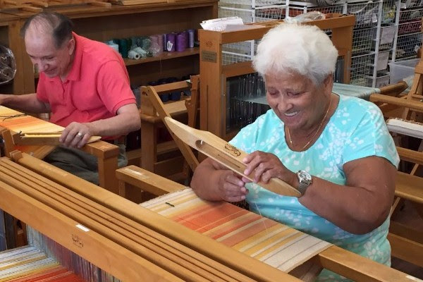 Photo of two residents weaving on looms