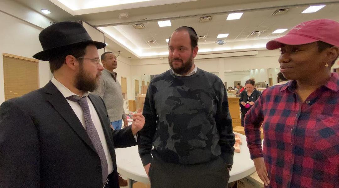 From left: Rabbi Moshe Z. Schapiro, Chesky Deutsch and Pam Johnson talk during the charity drive. (Courtesy of Benny Polatseck)