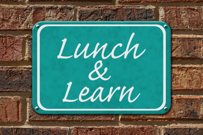 Lunch and Learn Sign A teal sign with the word Lunch and Learn on a brick wall