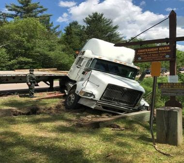 A large truck that has slipped down a small embankment