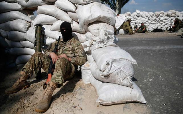 Un miliciano prorruso espera en un puesto de control cercano a Donetsk.