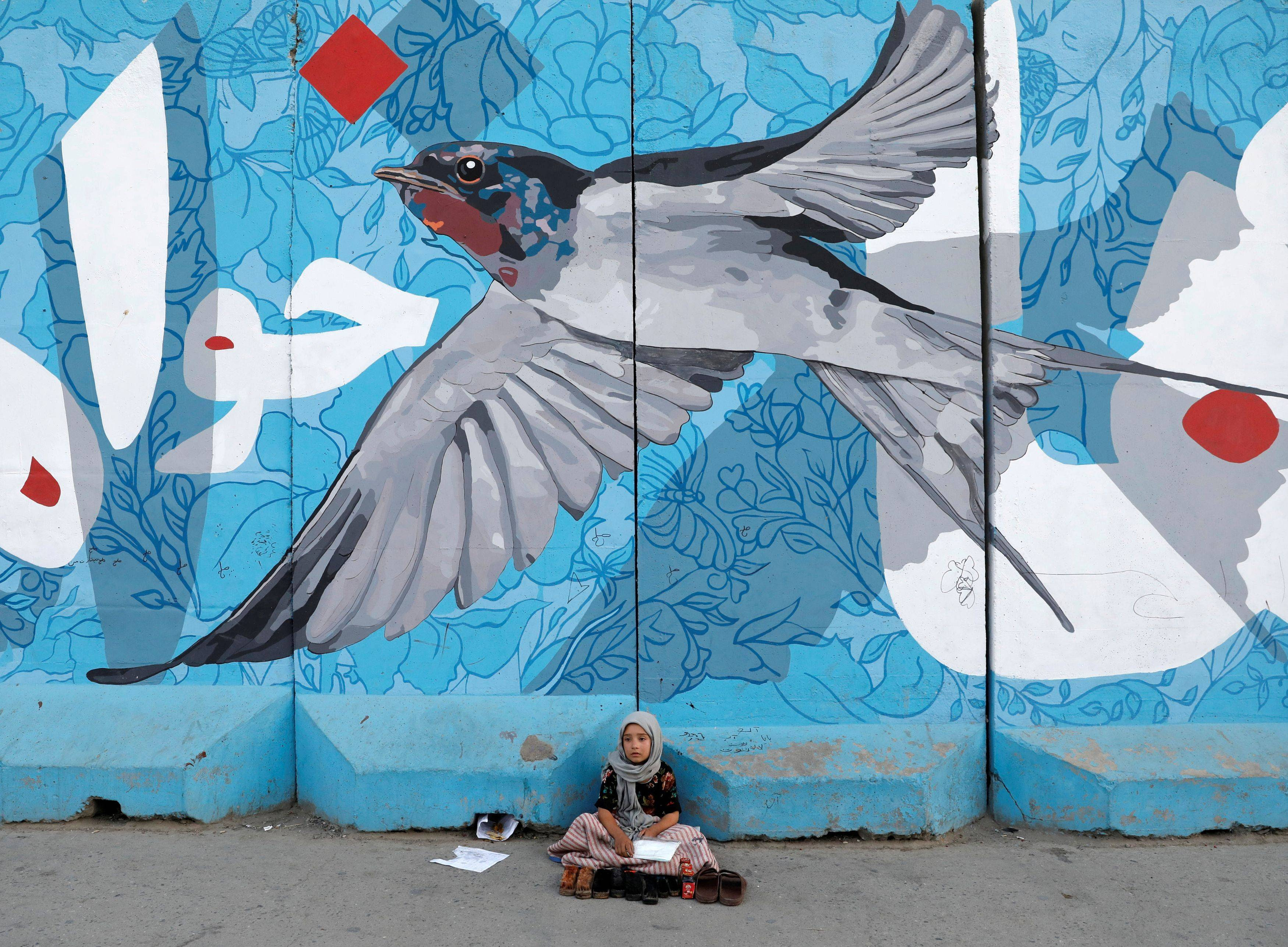 A girl who polishes shoes waits for customers under graffiti on a wall in Kabul on June 24, 2021. (Reuters)