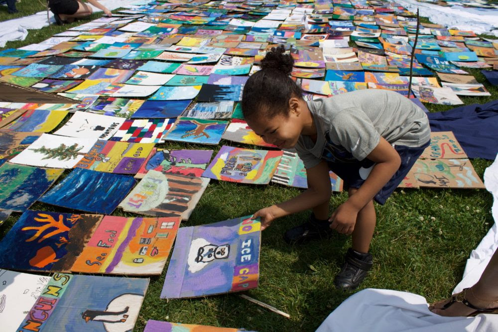 A young child examines every tile before placing them inside the whale mosaic on Boston Common. (Miriam Wasser/WBUR)