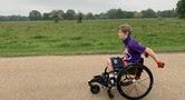 Image of a boy using his wheelchair to move through a park