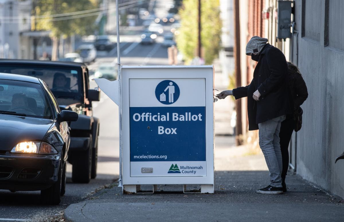 Voters return ballots to an Official Ballot Drop Box at the elections office from both the sidewalk and their cars.