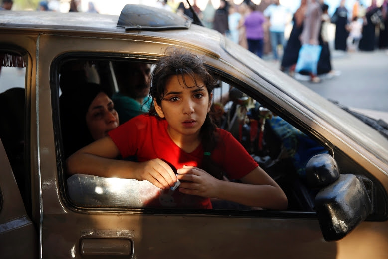 A Palestinian girl looks out from a vehicle while fleeing the Shujayeh neighbourhood during heavy Israeli shelling in Gaza City July 20, 2014. REUTERS/Finbarr O'Reilly