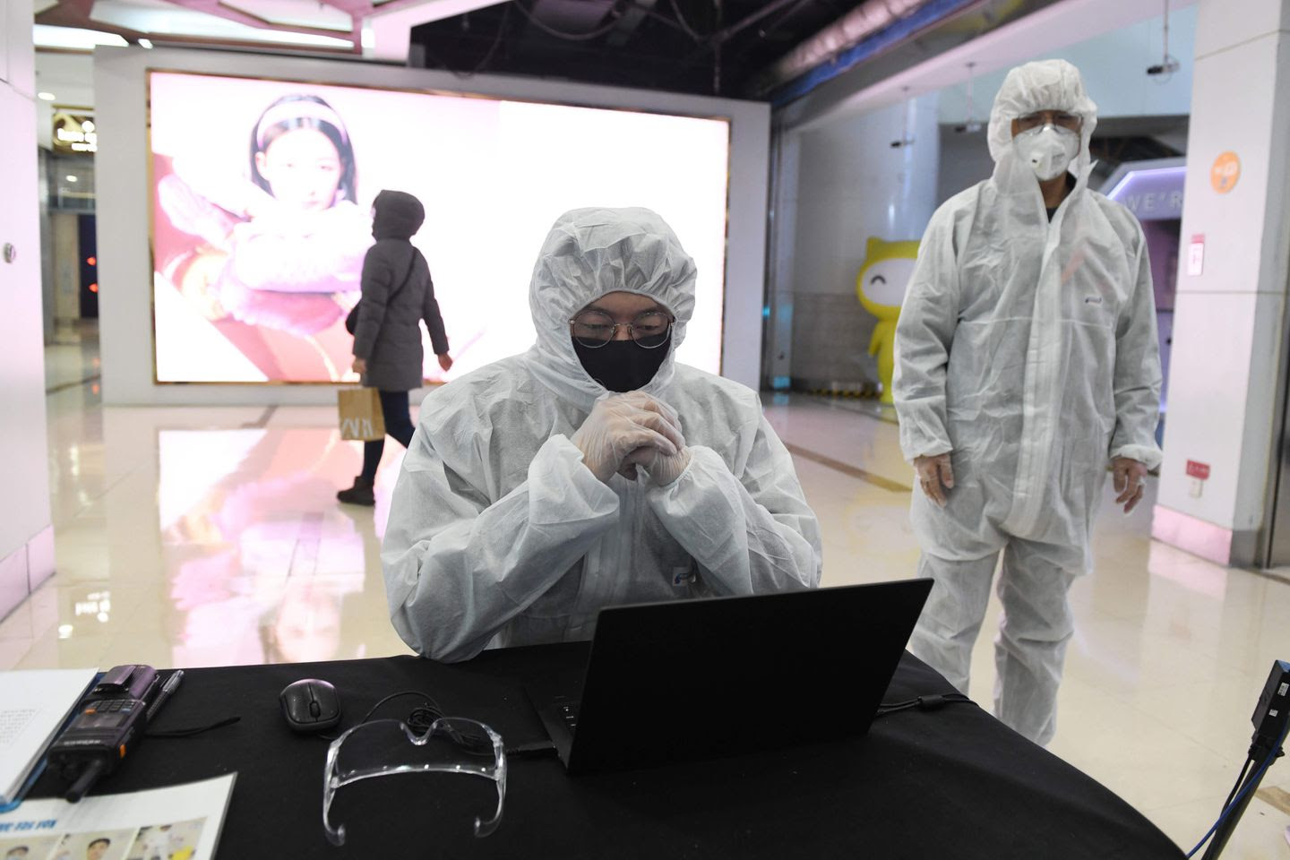 Security guards wore hazmat suits as they checked the temperature of arriving customers at a shopping mall in Beijing on Thursday.