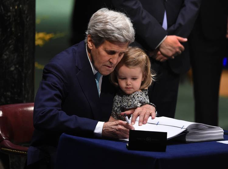 John Kerry signs the Paris climate agreement last year while holding his granddaughter. (Timothy A. Clary/AFP/Getty Images)
