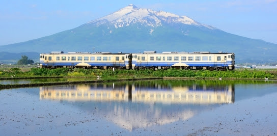 The background is Mt.Iwaki, and the two-cars train of Gono Line runs in the countryside, Aomori, Japan.