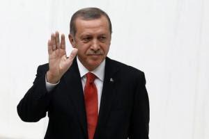 Turkey's President Tayyip Erdogan waves as he attends…