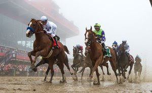 Justify (outside) and Good Magic (inside) battle past the stands for the first time in the Preakness Stakes
