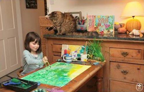 Iris Grace pinta observada pela gatinha Thula