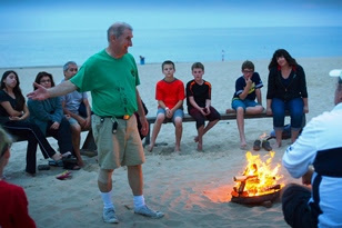 Campers sit by a fire on the beach.