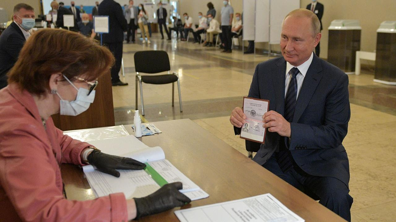 Russian President Vladimir Putin shows his passport to a member of a local electoral commission at a polling station on the last day of a weeklong nationwide vote on constitutional reforms in Moscow, Russia July 1, 2020.
