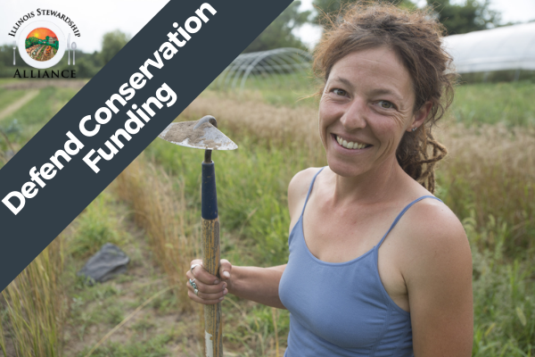Defending Conservation Funding  is a Primary Issue - Photo of Alliance member Andy Hazzard smiling, at her farm, standing in a field with a farming implement.