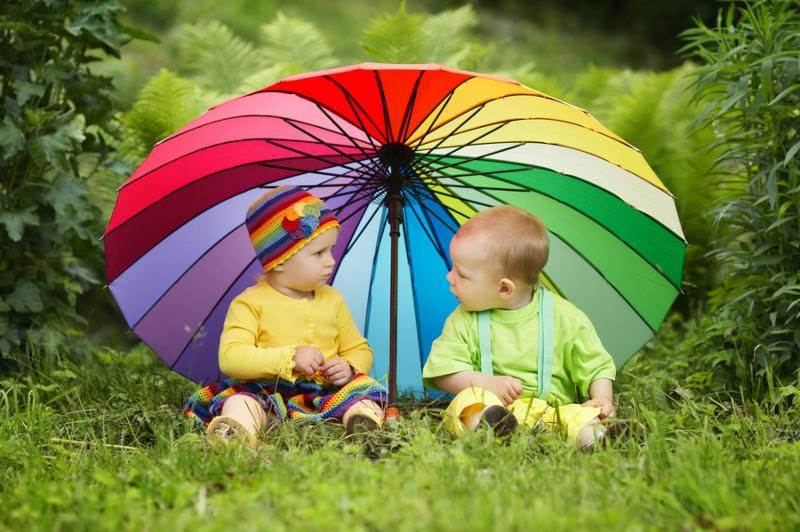 cute little children under colorful umbrella outdoors