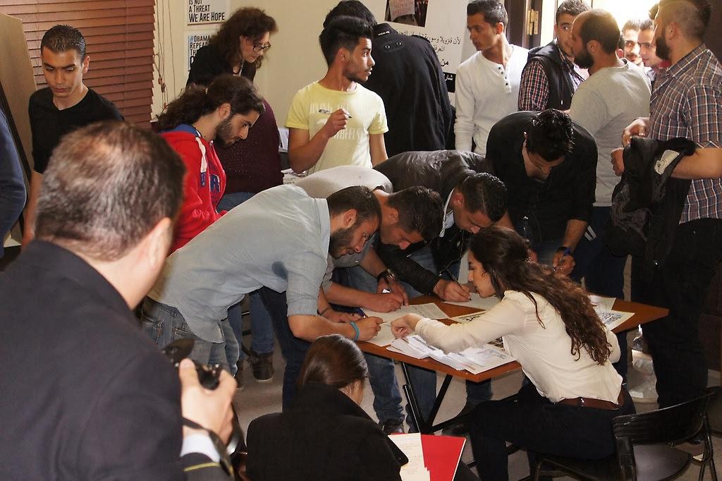 """La comunidad estudiantil y público asistente sirio manifestó su apoyo firmando los cuadernos de nuestra campaña en contra del """"Decreto Ejecutivo"""" del Gobierno de los EEUU."""