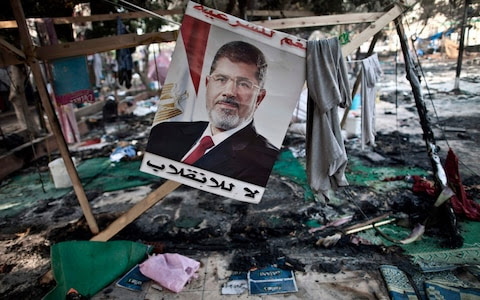 A photo taken on Aug 15, 2013 shows a portait of Mohamed Morsi, by then Egypt's ousted president, hanging admist debris at Rabaa al-Adawiya square in Cairo