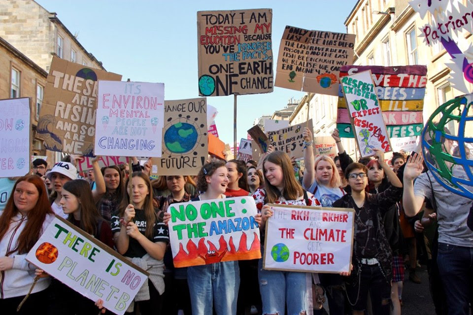 A group of schoolchildren at the front of a march, with one holding a sign which read 'The Rich get Richer and the Climate gets Poorer'.