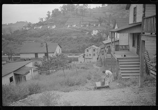 Coal miner's wife getting water from pump, company houses, Pursglove, Scotts Run, West Virginia