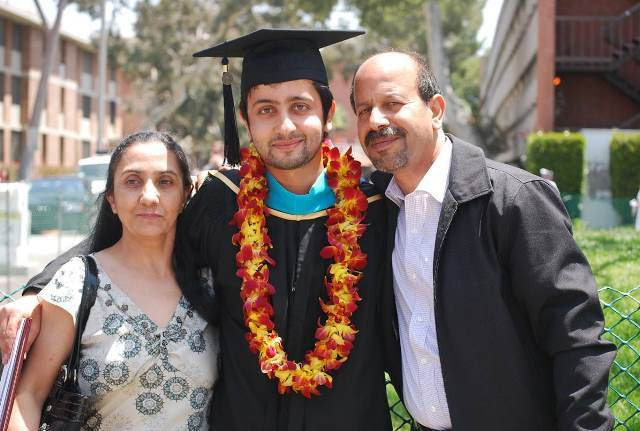 Naweed takes a photo with his mom and dad at graduation