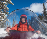 A female snowmobiler smiles at the camera.