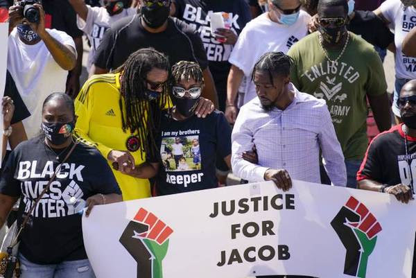 Jacob Blake's sister, Letetra Widman, center, and uncle Justin Blake, left, march at a rally in Kenosha on Aug. 29, 2020. (Morry Gash/AP)