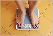 A young woman's feet on a bathroom scale.