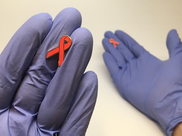 gloved hands with AIDS awareness ribbons