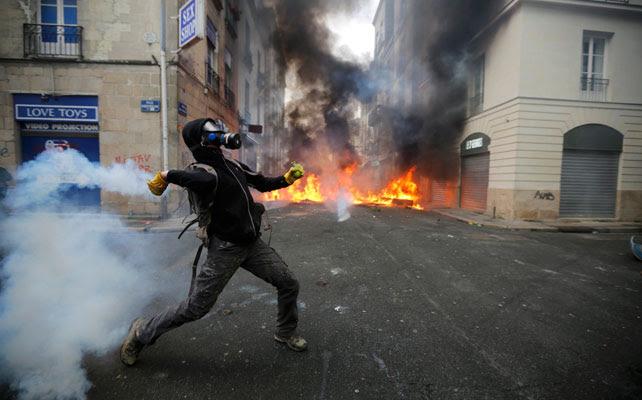 Un manifestante devuelve un bote de humo a lanzando por la Policía.