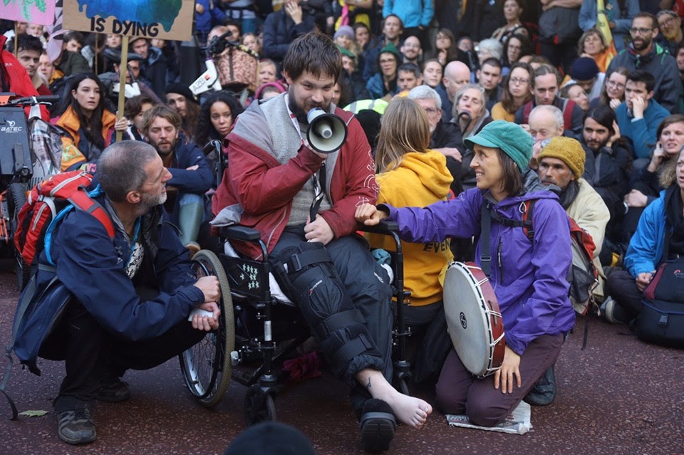 A rebel in a wheelchair, giving a speech with a megaphone. 2 rebels are sat either side of him, with a large group of rebels sat behind them listening to the speech.