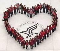 image from high above of several dozen people wearing red forming the shape of a heart around the HHS seal