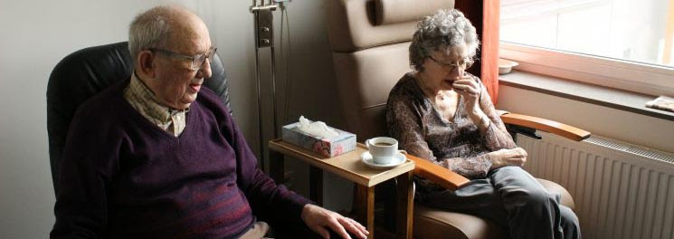 Two old people sitting in care home