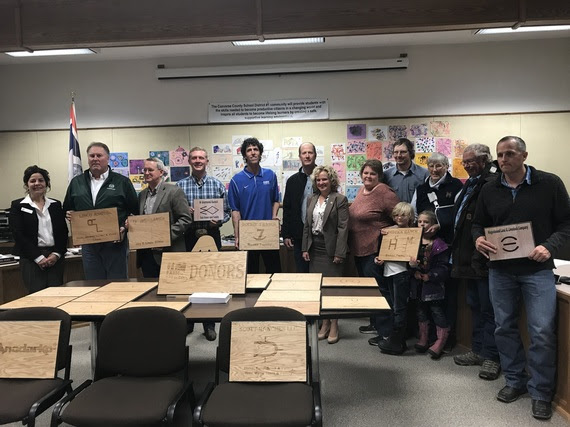 State Superintendent Jillian Balow stands with Converse County School District #1 board members and local donors while holding the signs recognizing their donations to the school district.