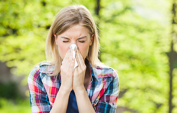 A woman outside sneezing into a tissue.
