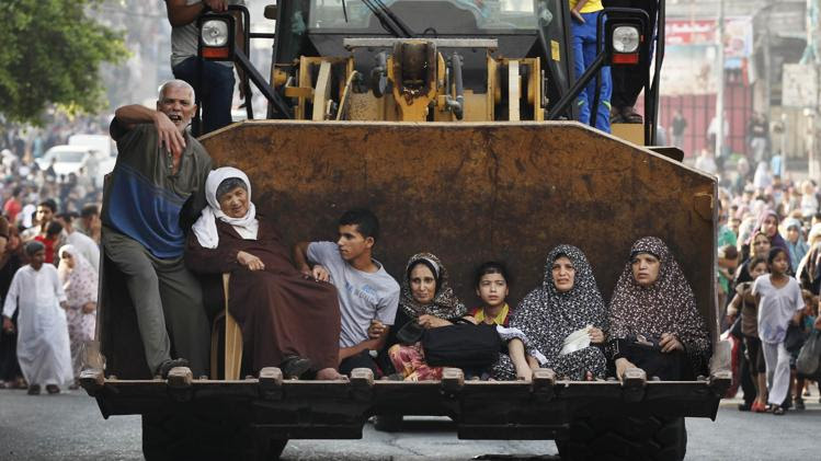 Palestinians sit in the bucket of an excavator as families flee the Shujayeh neighbourhood during heavy Israeli shelling in Gaza City July 20, 2014. REUTERS/Finbarr O'Reilly