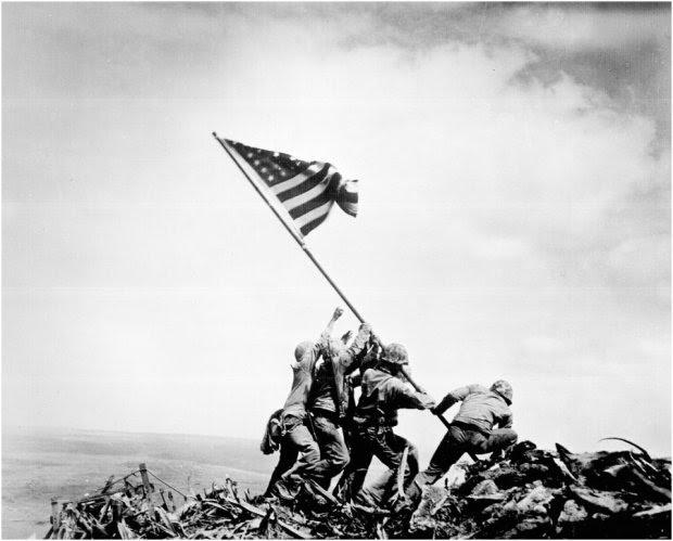 Iwo Jima-23 Φεβρουαρίου 1945: Έξι Αμερικανοί πεζοναύτες τοποθετούν μια σημαία κατά τη διάρκεια της μάχης στην Iwo Jima. Τρεις από αυτούς τους άνδρες, σκοτώθηκαν αργότερα στη μάχη. Η συγκεκριμένη εικόνα θυμίζει το τέλος του Β 'Παγκοσμίου Πολέμου και ενέπνευσε την κατασκευή του περίφημου μνημείου στην  Ουάσιγκτον.