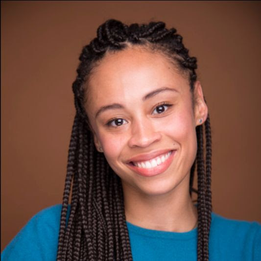 Development Fellow Mykel Nairne is an African-American woman with her hair in long, dark brown braids. She is wearing a turquoise top and is smiling at the camera.