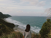 A girl looking out over the beach from up a hill