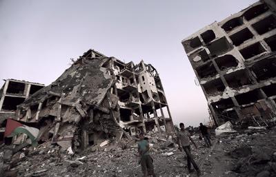 Palestinos caminan entre los escombros de lo que fueron las torres de AL-Nada.- MOHAMMED SABER (EFE)