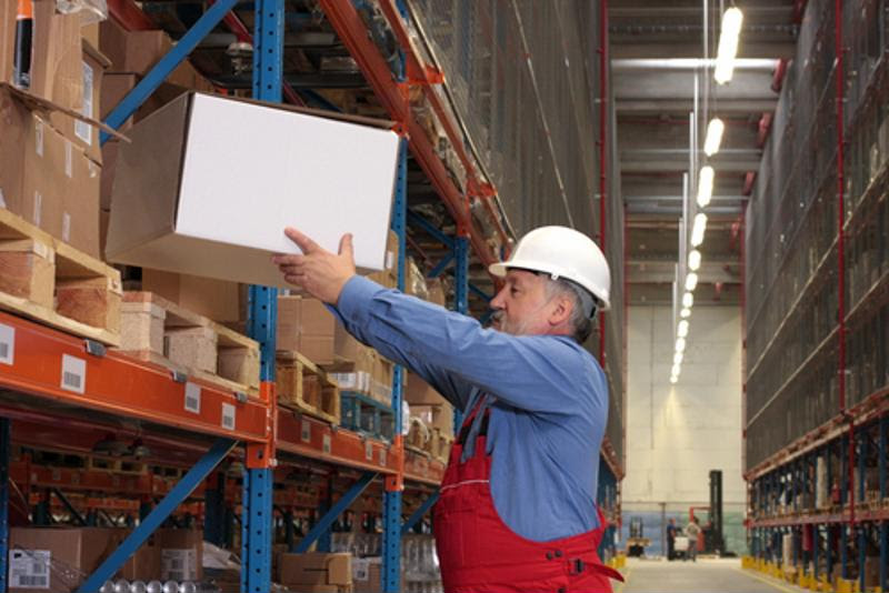 A warehouse worker lifts a box,