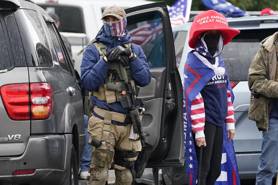 One supporter of President Trump holds a gun as another a baseball bat in front of the Oregon State Capitol building Saturday, Nov 7, 2020, in Salem, Ore., after Democrat Joe Biden defeated Trump to become 46th president of the United States. (AP Photo/Marcio Jose Sanchez)