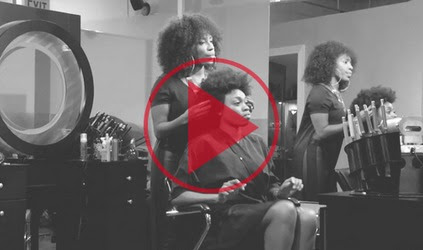Black women at a salon respond to a man in a suit that tells the hair stylist to straighten their hair?