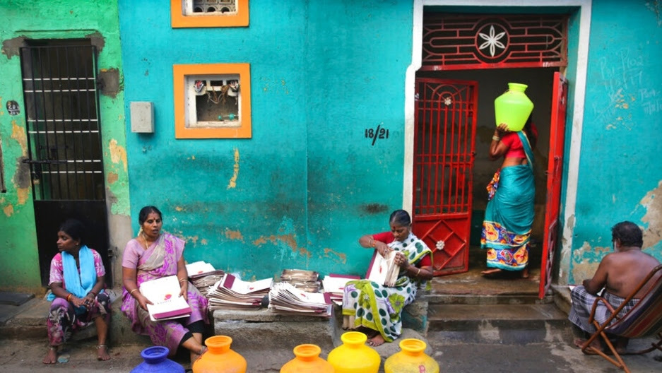 In this July 15, 2019, photo, a woman walks into a house with a vessel of drinking water filled from a water truck in Chennai in Southern Indian state of Tamil Nadu.