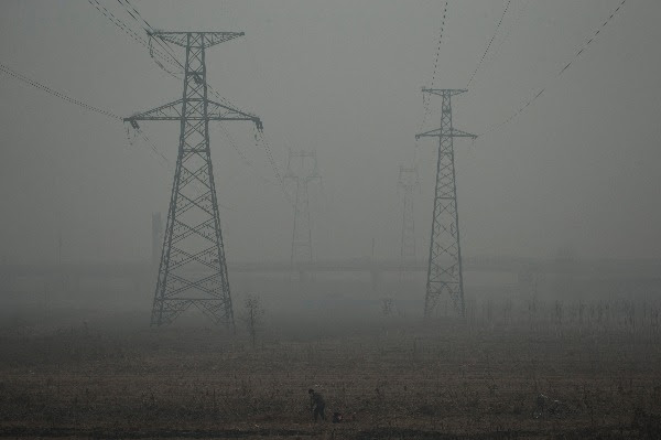 Image: A farmer shovels in a field near electric pylons in heavy haze on a severely polluted day in Shijiazhuang, in northern China's Hebei province, Wednesday, Feb. 26, 2014.