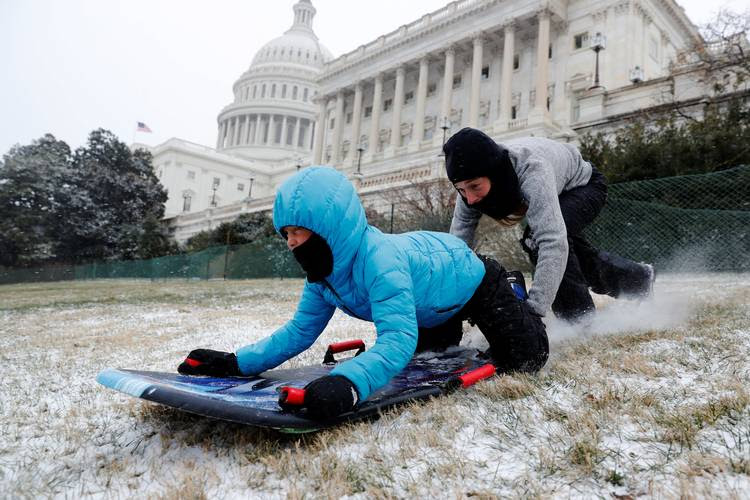 Diego Vazquez gets a push from his mother Genevieve Vazquez in an attempt at sledding in a light snowfall on the west front of the U.S. Capitol. (Jonathan Ernst/Reuters)