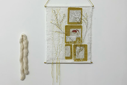 A photograph of a textiles wall hanging by Camban Studio. It is white, with brown and white square details on the right, and floral brown details across. It is displayed on a white wall and next to a strip of white wool.