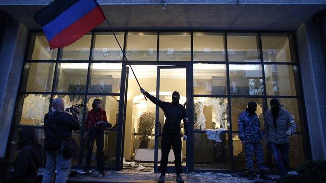 Un miliciano prorruso ondea una bandera de Donbass tras tomar un edificio oficial en esta ciudad oriental de Ucrania.