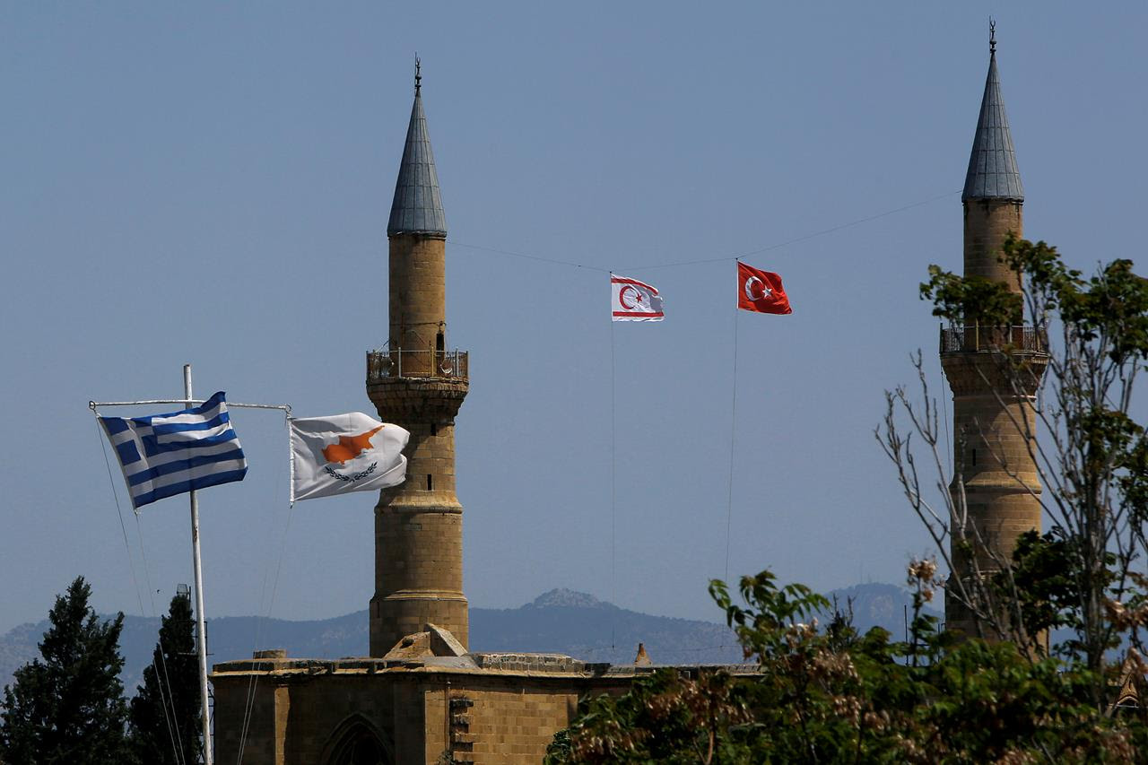Greek and Cypriot flags (L) flutter on poles in the southern area, as Turkish and Turkish Cypriot breakaway flags (R) fly between minarets in the northern Turkish-occupied area, within Cyprus's divided capital Nicosia, April 26, 2021.